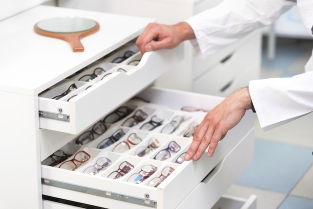Ophthalmologist hands close up, choosing glasses from a drawer in the optical store Premium Photo