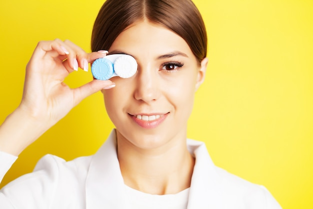 The ophthalmologist holds a container with contact lenses near the eyes Premium Photo