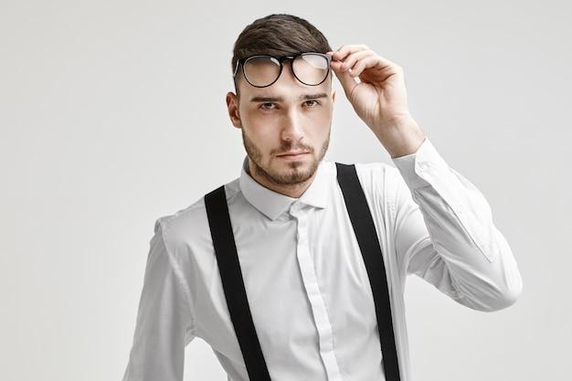 Ottica, occhiali e concetto di moda. immagine del giovane maschio brunetta con la barba lunga bello che indossa camicia bianca formale con bretelle, fissando la telecamera con sguardo scrutatore, sollevando gli occhiali Foto Gratuite