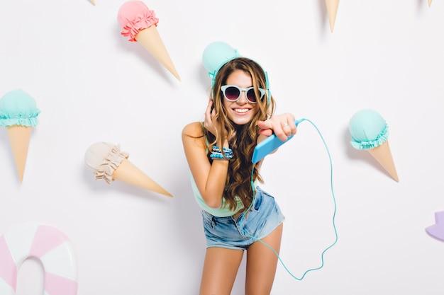 誠実な笑顔で探しているトレンディなアクセサリーを着て日焼けした肌を持つ楽観的なブルネットの少女。アイスクリームで飾られた壁で音楽を楽しんで笑っている若い女性の肖像画。 無料写真