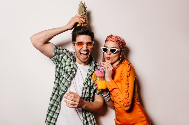 Оптимистичная пара в стильной летней одежде отдыхает и наслаждается коктейлем и ананасом. Бесплатные Фотографии