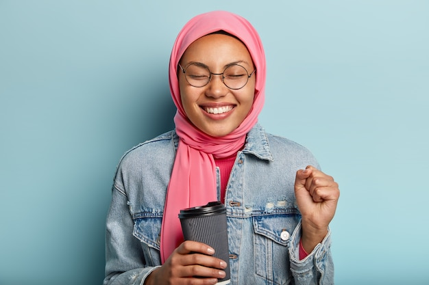 Optimistic lovely muslim woman clenches fist, closes eyes from pleasure Free Photo