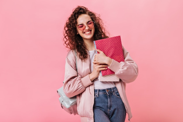 Optimistic woman in silk jacket and jeans holding notebooks Free Photo