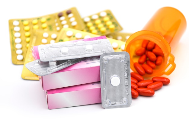 Oral contraceptive pill, emergency pilll and vitamin pill on white background. Premium Photo