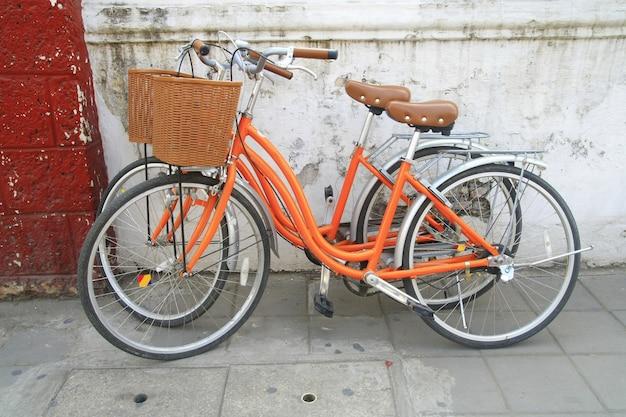 Orange bicycle park near wall Premium Photo