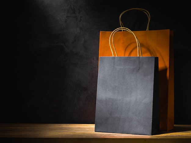 Orange and black paper shopping bags on wooden table Premium Photo
