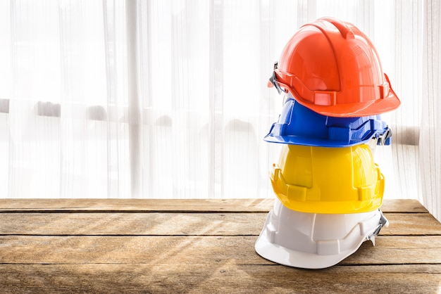 Orange, blue, yellow, white hard safety helmet construction hat for safety project of workman as engineer or worker Premium Photo