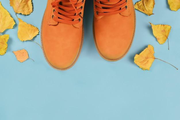 Orange brown mens autumn boots on grey pastel. top view, copy space. Premium Photo