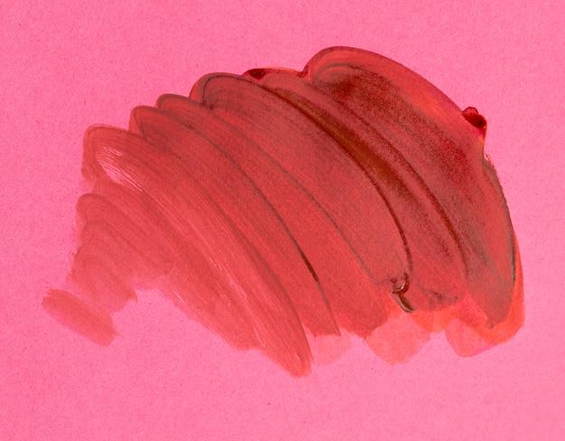Tratto di pennello arancione su sfondo rosa Foto Gratuite
