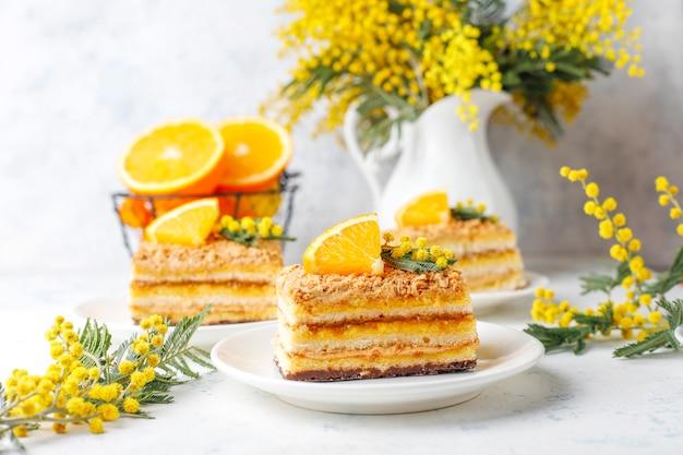 Апельсиновый торт украшен свежими дольками апельсина и цветами мимозы на свете Бесплатные Фотографии
