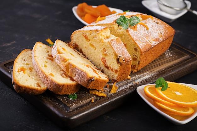 Torta all'arancia con albicocche secche e zucchero a velo. Foto Gratuite