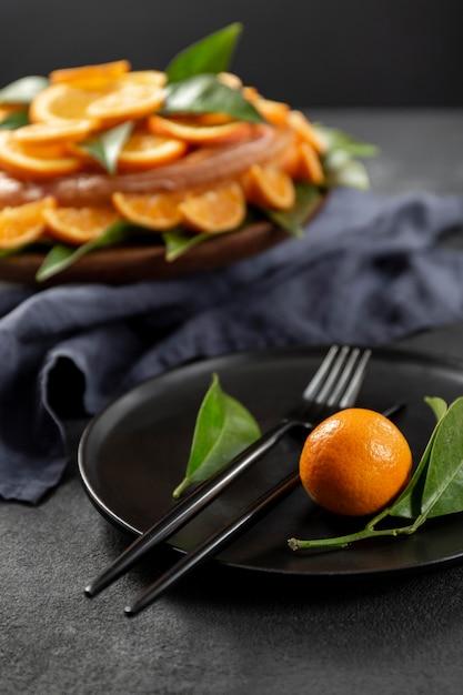 葉とカトラリーとオレンジ色のケーキ 無料写真