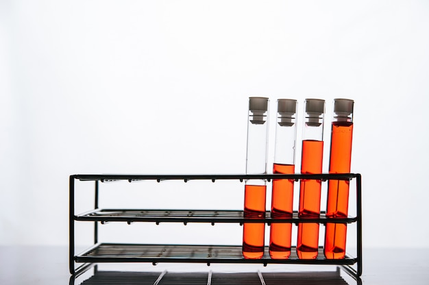 Orange chemicals in a science glass tube arranged on a shelf Free Photo
