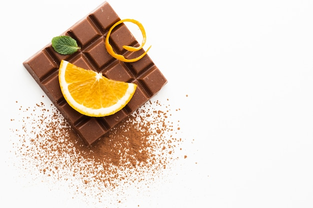 Orange and chocolate on plain background Free Photo
