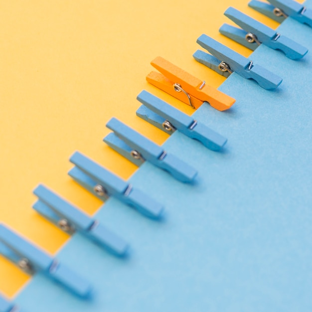 Orangeclothespin surrounded by blue ones Free Photo