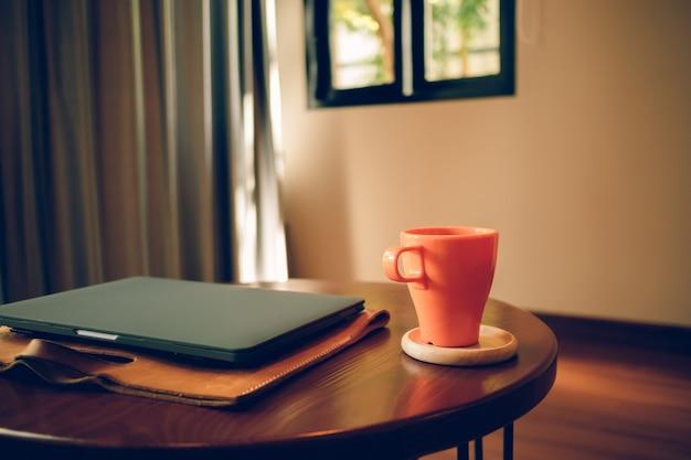カフェのテーブルにオレンジ色のコーヒーカップとノートパソコン。 Premium写真