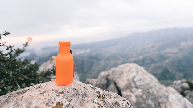 An orange colored water bottle on top of rocky mountain Free Photo