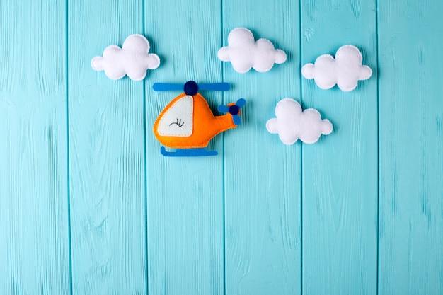 Оранжевый вертолет и облака ремесла на голубой деревянной предпосылке с copyspace. войлочные игрушки ручной работы. Premium Фотографии