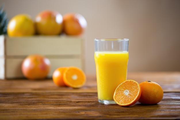Апельсин разрезанный пополам, лежа на деревянном столе рядом со стаканом свежевыжатого сока Premium Фотографии