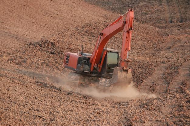 Orange excavator under construction large reservoir, dust by digging the soil. Premium Photo