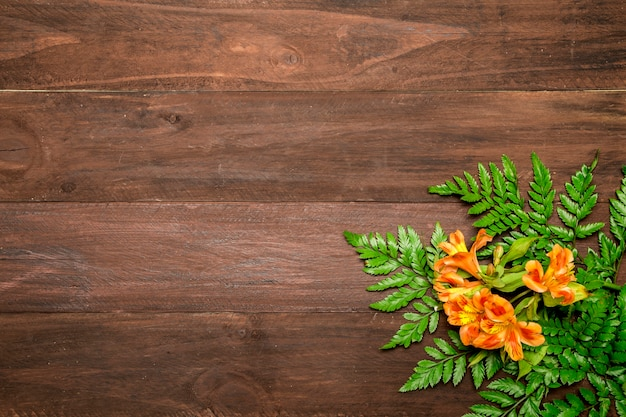 Orange flowers with leaves on wooden background Free Photo