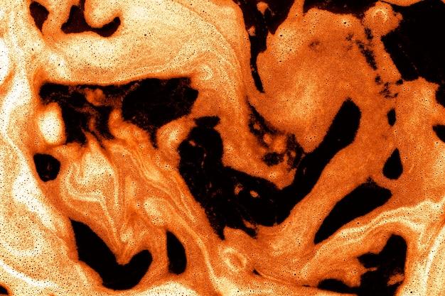 Orange foam on top of liquid Free Photo