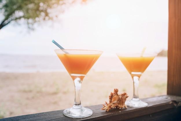 木製の端にオレンジ色の新鮮なエキゾチックなカクテル。眼鏡の間に横たわるシェル。島の生活 Premium写真