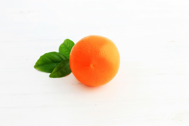 Orange fruit and one cut in half, with leaf isolated on white background. Premium Photo