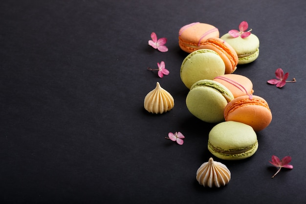Orange and green macarons or macaroons cakes on black background, side view, copy space. Premium Photo