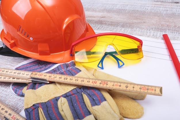 Orange hard hat, safety glasses, gloves and measuring tape Premium Photo