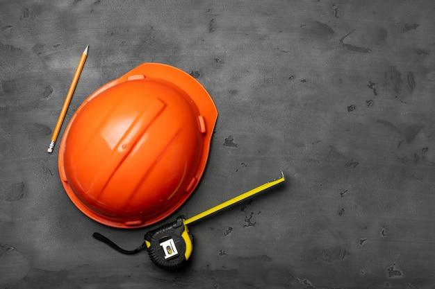 오렌지 Hardhat, 눈금자 및 연필 검은 상단보기 프리미엄 사진