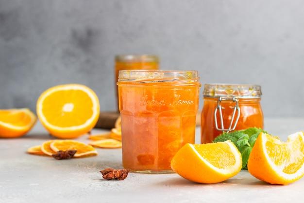 Orange jam in glass jar, orange fruit slices, mint and spices on light grey Premium Photo