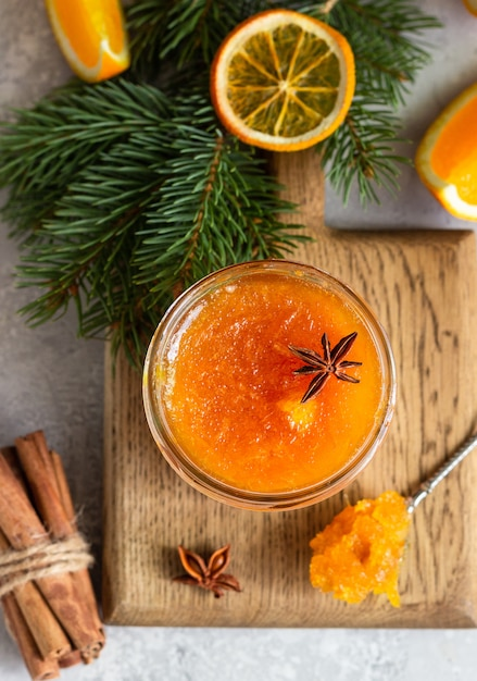 Orange jam in a glass jar with winter spices and fir branches. Premium Photo