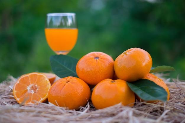 Апельсиновый сок и апельсиновые фрукты на деревянной коробке и соломе на размытом зеленом фоне боке. витамин с, железо, фосфор помогают организму хорошо выводить из организма. Premium Фотографии