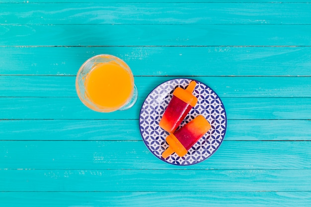 Orange juice and bright fruit popsicle on plate on wooden surface Free Photo