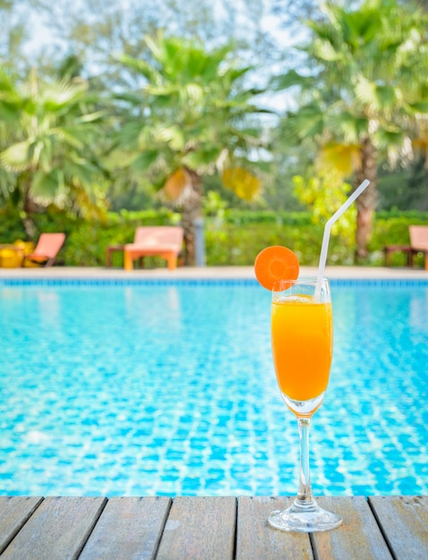 Orange juice glass on wooden table with swimming pool view background Premium Photo