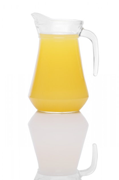 Orange juice in a jug with handle standing on mirror surface isolated on white Premium Photo