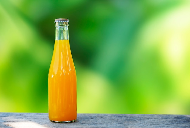 Orange juice packed in glass bottles table top made of wood and green nature background Premium Photo
