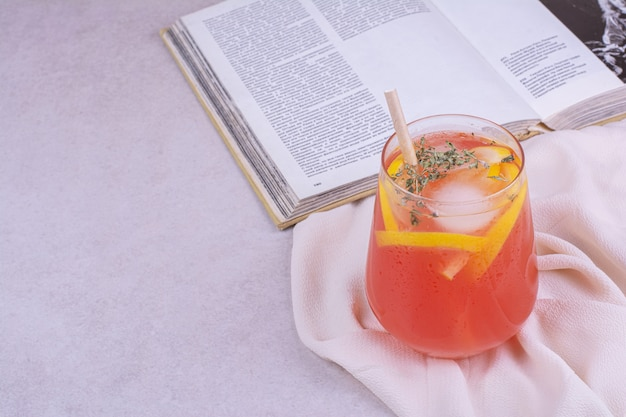 白いテーブルにフルーツスライスとスパイスとオレンジジュース。 無料写真