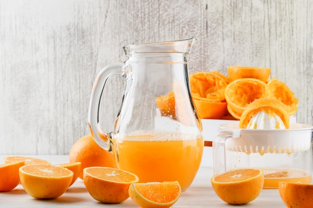 Orange juice with oranges, squeezer in a jug on white surface Free Photo
