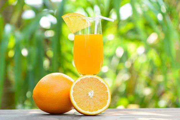 Orange juice with piece orange fruit on glass with nature green summer background Premium Photo
