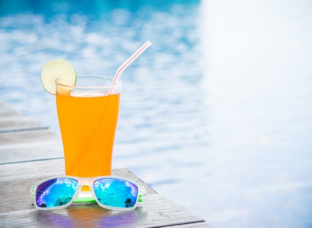 Orange juice with sunglasses at the side of swimming pool. vacation, summer  concept Premium Photo