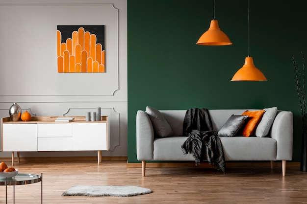 Orange lamps above grey couch in black living room interior with poster above cabinet Premium Photo