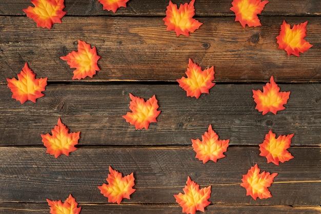 Orange leaves arrangement on wooden background Free Photo