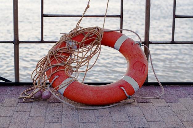 Orange lifebuoy with rope on the pier Premium Photo