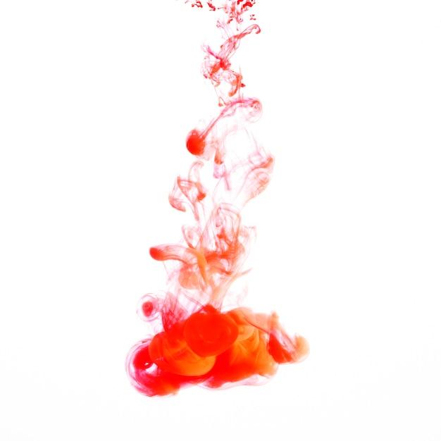 Orange light ink droplet flowing in water Free Photo