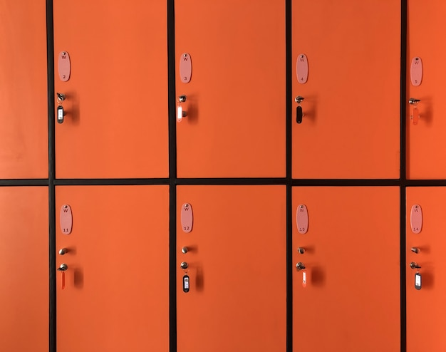 The orange  lockers in gym have many doors locked with keys for private safety Premium Photo