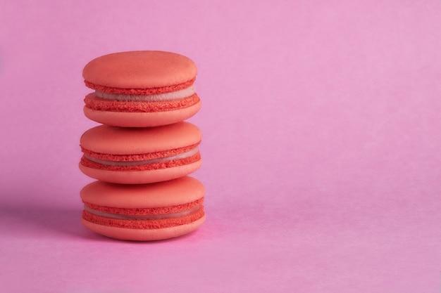 ピンクの背景にオレンジ色のマカロン Premium写真