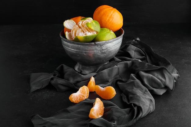 黒い表面の金属製のカップにオレンジみかん。 無料写真