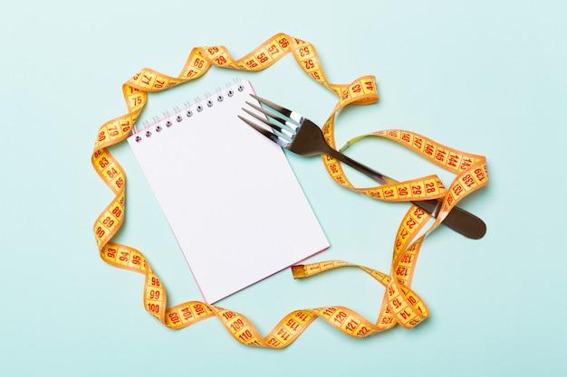Orange measure tape, open notebook and fork Premium Photo